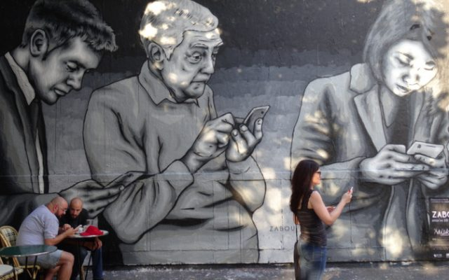 graffiti of people checking their smartphones